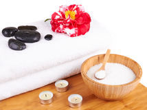 Spa setting with candles, camellia flower, towel, salt and stone stock photo