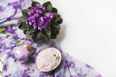 Spa setting with cosmetic cream, bath salt and African violet in flower pot on white wooden table background. Selective focus Stock Images