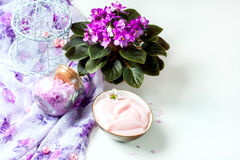 Spa setting with cosmetic cream, bath salt and African violet in flower pot on white wooden table background. Selective focus Royalty Free Stock Photography