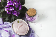Spa setting with cosmetic cream, bath salt and African violet in flower pot on white wooden table background. Selective focus Stock Image