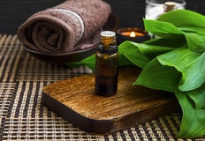 Spa setting with essence bottle, towel and candle Royalty Free Stock Image