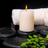 Spa setting of green branch fern, towels and candle on zen stone Stock Photo