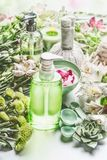 Spa setting with green cosmetic bottle product with pump dispenser , flowers and herbs, beauty tools and accessories. For skin and body care royalty free stock images