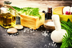 Spa setting with herbal massage ball, flowers and essential oil Stock Images