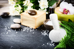 Spa setting with herbal massage ball, flowers and essential oil Stock Image