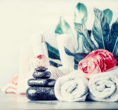 Spa setting with hot black basalt massage stones ,flowers , towels and palm leaves, front view Stock Images