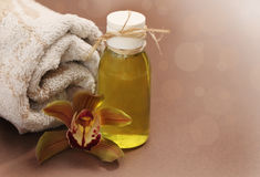 Spa setting with massage oil. Spa setting with orchid, towel and massage oil Royalty Free Stock Photos