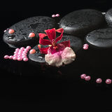 Spa setting of orchid cambria flower on zen stones with drops Royalty Free Stock Image
