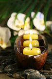 Spa setting with pebbles, candles and flowers Royalty Free Stock Photos