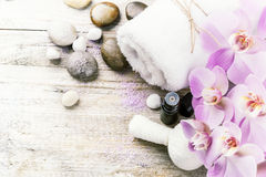 Spa setting with pink orchid, herbal massage ball and essential Stock Photo