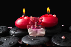 Spa setting of red candles on zen stones with drops, orchid Stock Photos