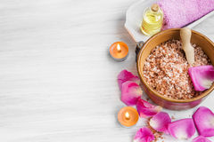 Spa setting with rose bath salt, rose petals and oil with burnin Stock Image