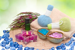 Spa setting. Sea salt in bowl, bottles with aroma oil, towels and candles Royalty Free Stock Photos
