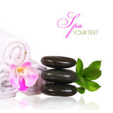 Spa setting. Spa Stones and Pink Orchid Flower with Green Leaves. And Towels isolated on white. Zen pebbles Stock Images