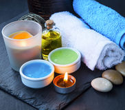 Spa setting with towels,face mask, bath salt and oil and candle Stock Photos
