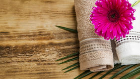 Spa setting with towels and pink flower Royalty Free Stock Photography