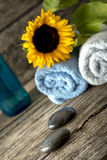 Spa setting with a towels, sunflower on top, massage stones, and Stock Photo