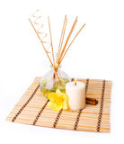 Spa setting on white background. Spa setting with aroma sticks, candle, yellow flower and cinnamon on bamboo mat isolated on white Stock Image