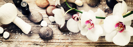 Spa setting with white orchid, herbal massage ball and essential Royalty Free Stock Photography