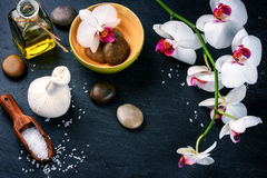 Spa setting with white orchid, herbal massage ball and essential Stock Photos