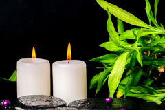 Spa setting of zen basalt stones with drops, white candles, bead Stock Image