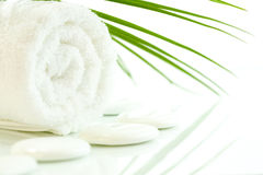 SPA settings. White pebbles, towel and palm leaf over white. Selective focus stock photo