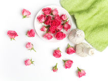 Spa settings. Fresh roses in a plate and herbal compress. Flat lay. Top view Stock Image