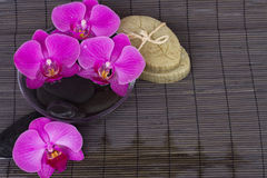 Spa settings with orchids on bamboo mat Royalty Free Stock Image