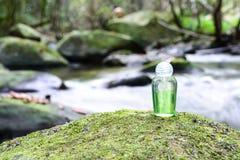 Spa shampoo on moss stone with waterfall background.  Stock Photo