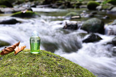 Spa shampoo on moss stone with waterfall background.  royalty free stock photo