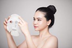 Spa sjukvård Kvinna med att rena maskeringen på hennes isolerade framsida royaltyfri fotografi