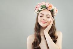 Spa skönhetstående av den nätta modellkvinnan med sund hud, lockigt hår och blommor på hennes huvud arkivbilder