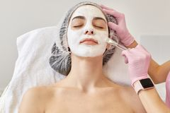 Spa and skin care concept. Young woman with facial mask in beauty salon, cosmetologist using special brush for applaying cream on royalty free stock images