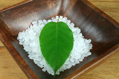 Spa slill life. Spa still life - salt crystals and green leaf in wooden bowl Stock Photos