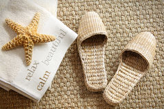 Spa slippers on seagrass carpet with towels. And starfish Royalty Free Stock Image