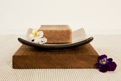 Spa still life. With organic soap bar, flower blossom on a beautifull ceramics plate on wood Royalty Free Stock Photos