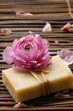 Spa still life. Ranunculus flower with petals and handmade soap on mat Royalty Free Stock Image
