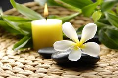 Spa still life. Frangipani flower and candle and bamboo leaves on woven mat Royalty Free Stock Photos