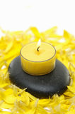 Spa still life. Burning yellow candle on stone with yellow flower petals Stock Images