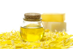 Spa still life. Handmade Soap and bottle of massage oil on yellow flower peals Stock Photos