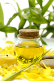 Spa still life. Massage oil and handmade Soap on yellow flower peals Royalty Free Stock Photos