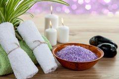 SPA still life with aromatic burning candles, stones, towel and lavender bath salt. On wood Royalty Free Stock Images