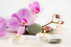 Spa still life with aromatic candles flower and stones. Spa still life with aromatic candles, orchid flower and stones Royalty Free Stock Photography