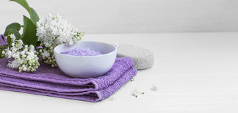 Spa still life with bath salt. Lilac flowers and towels Royalty Free Stock Images