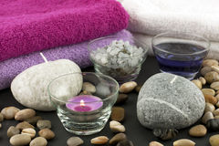 Spa still life with bath towels, candles and stones. Spa composition with colorful candles and towels Stock Image
