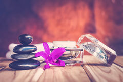 Spa still life black rocks with purple orchids and lotion. Royalty Free Stock Photography