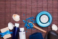 Spa still life in blue colors with bottles, soap and sea salt Royalty Free Stock Images