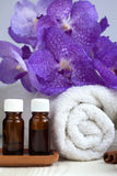 Spa still life with orchid flower, towel, aromatic oils Royalty Free Stock Images
