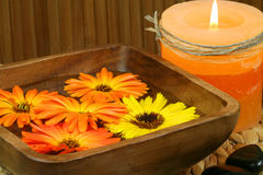 Spa still life - flowers and candle. Orange marigold flowers floating in wooden bowl, burning candle and stones. Spa still life Stock Images
