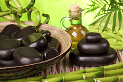 Spa still life with hot stones. And essential oil Stock Photos